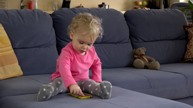 baby girl use modern smart mobile phone sit on sofa in room. FullHD video
