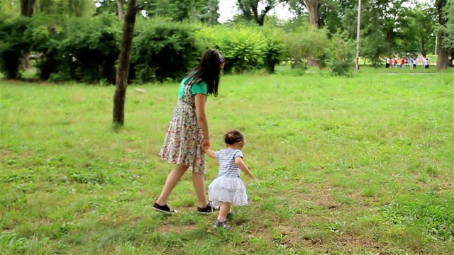 Baby girl walking in the park with sister support video