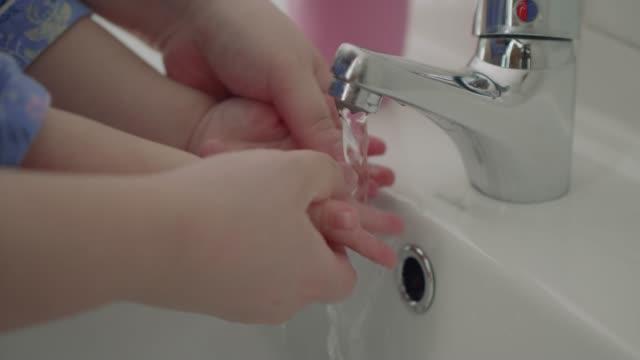 baby girl washing hand - myć filmów i materiałów b-roll
