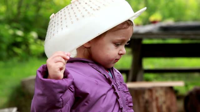 Baby girl wearing plastic colander on her head