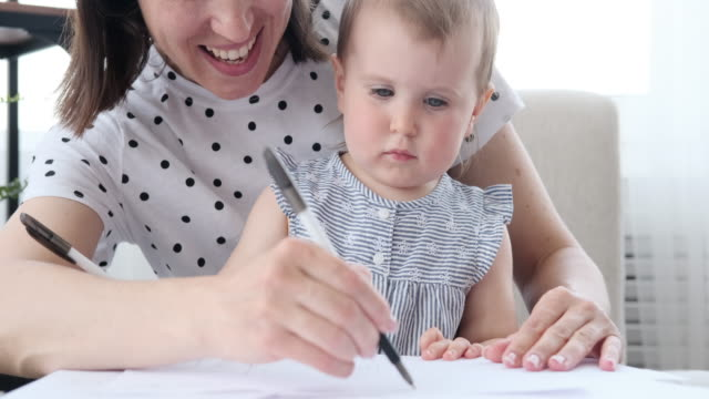 Baby girl with mother drawing on paper
