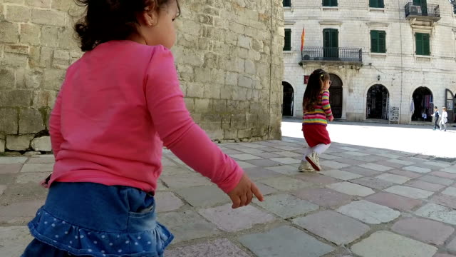 baby girls walking along the narrow street of the old town - mika video stock e b–roll