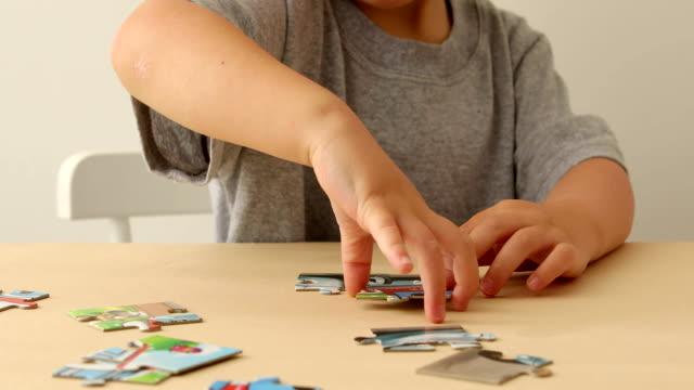 vídeos de stock e filmes b-roll de baby hand fold puzzle - quebra cabeças