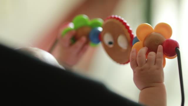vídeos de stock, filmes e b-roll de mãos do bebê que jogam com berço da cadeira do brinquedo - mobile