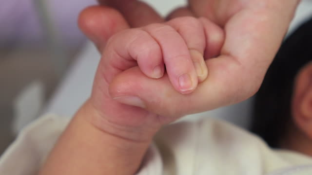 Baby holding mother hand video