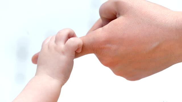 baby holding mother's finger - fiducia video stock e b–roll