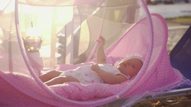 Baby in pink bassinet outdoor in summer