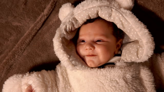 Baby in plush teddy bear custume lay on the blanket - video