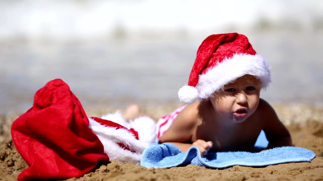Baby in Santa Claus hat on the beach