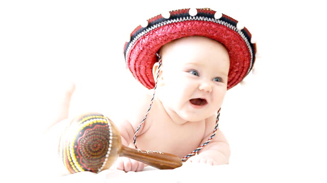 Baby in sombrero hat with maracas on the light background video