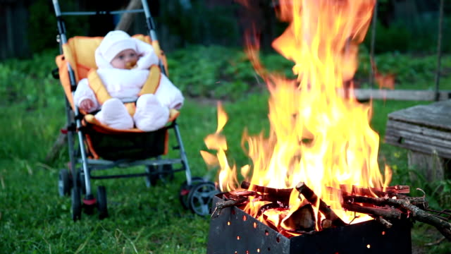 Baby in the pram sitting in front of the campfire video
