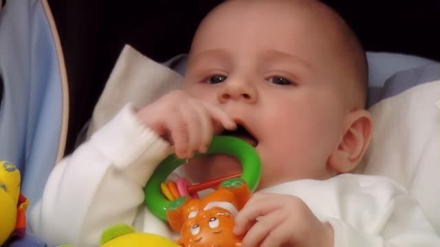 Baby in the pram sucks a rattle - medium shot medium shot sideways glance stock videos & royalty-free footage