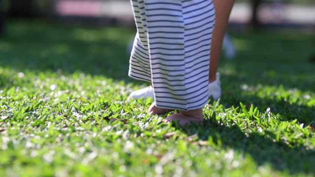 Baby infant learning to walk outside. Child stepping in grass