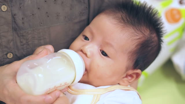 Baby infant suckling milk from bottle video