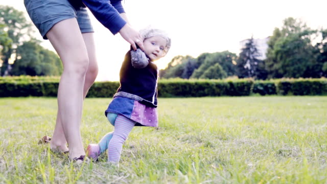 Baby is making first steps on the field in the park against the sunset, slow motion video