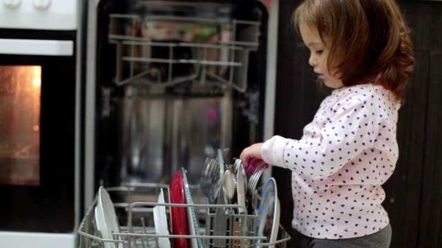 Baby is playing with a kitchen brush around dishwasher Baby is exploring and playing in the kitchen dishwasher stock videos & royalty-free footage