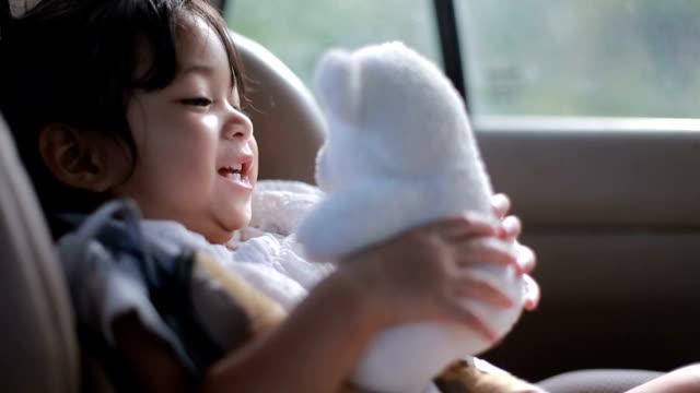 baby sitzt auf auto-kindersitz und spielen mit ihren teddybär - menschlicher kopf stock-videos und b-roll-filmmaterial
