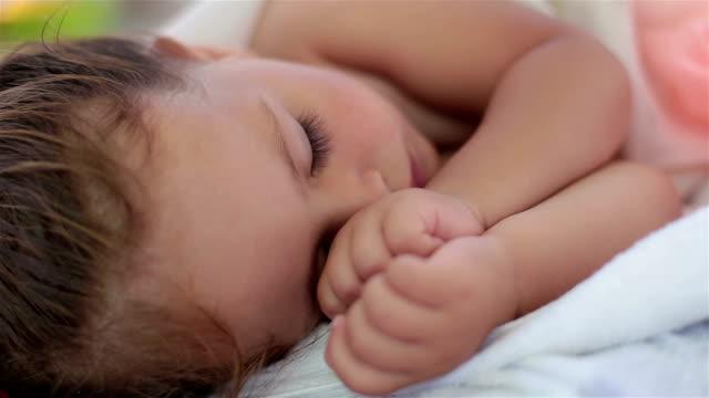 vídeos de stock e filmes b-roll de baby is sleeping outdoors on a beach - dormitar