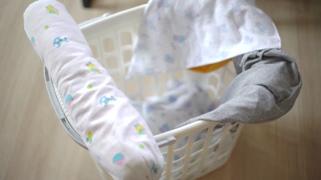 Baby Laundry piled in a basket 4K Video by CU Dolly right Camera and selective focus with color grading. Use for background clip or insert shot of Baby  Laundry piled in a basket laundry basket stock videos & royalty-free footage