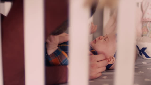 A baby laying in a crib and crying when her mother picks her up video