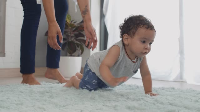 Baby learning how to crawl walk move Baby boy crawling on rug carpet with mother parent in background helping, involved parenting crawling stock videos & royalty-free footage