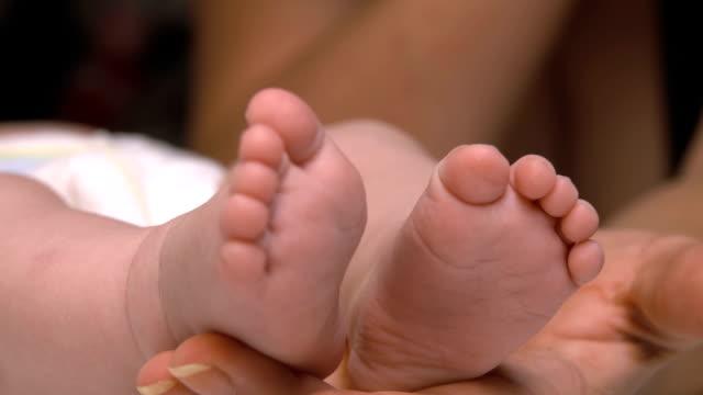 stockvideo's en b-roll-footage met baby benen op de palm van een volwassene - lood