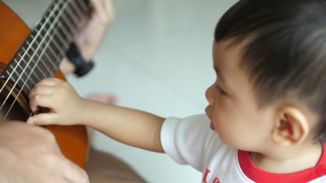 Baby listening Guitar hero Baby listening Guitar hero, 4K autism stock videos & royalty-free footage