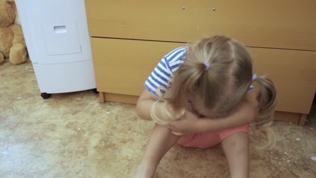 vídeos de stock e filmes b-roll de baby little girl crying  sits on the floor in room. - criança perdida