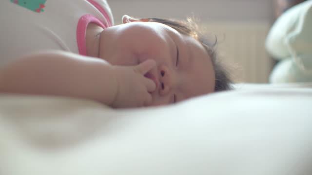 bambino disteso su un letto e suona - soltanto neonati video stock e b–roll
