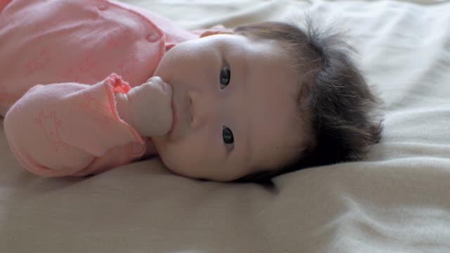 bambino disteso su un letto e fatica sua mano - soltanto neonati video stock e b–roll