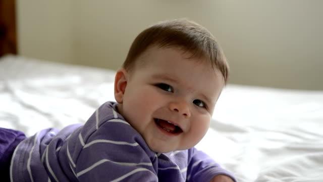 vidéos et rushes de bébé allongé sur le lit, souriant - 0 11 mois