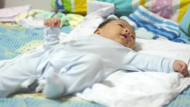 vidéos et rushes de bébé allongé sur le lit - 0 11 mois