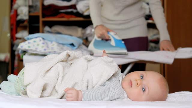 vidéos et rushes de bébé couché tranquillement sur le lit et sa mère est repassage - allongé sur le dos