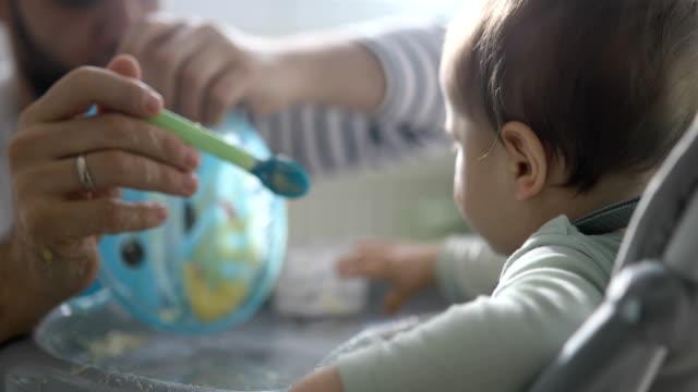 vídeos de stock, filmes e b-roll de bebê fazendo grande bagunça enquanto come - desarrumado