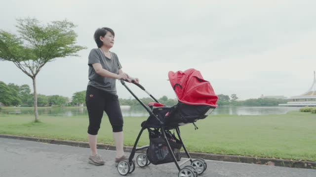 Baby; Mother walking and Pushes Baby Boys in Stroller. Baby; Mother walking and Pushes Baby Boys in Stroller at public park of Bangkok, Thailand. 4K Resolution. woman pushing cart stock videos & royalty-free footage