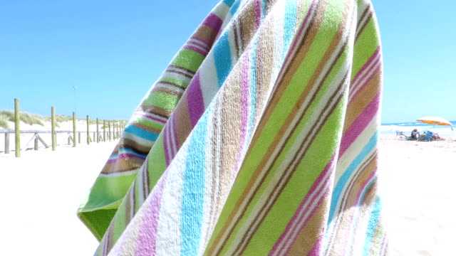 baby playing and wrapping in beach colorful towel slow motion - avvolto video stock e b–roll