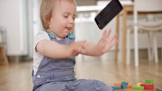 slo-mo-baby mit einem mobiltelefon spielen und warf es dann auf den boden - menschliche erzeugnisse stock-videos und b-roll-filmmaterial