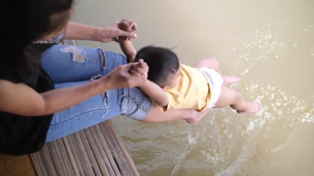 baby spielt mit mutter in der nähe von teich - weißrussland stock-videos und b-roll-filmmaterial