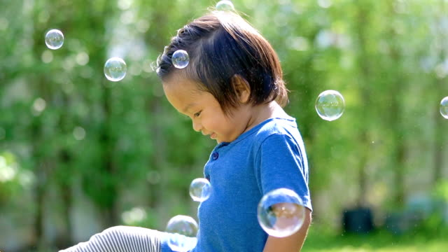 Baby playing with soap bubbles outdoors.