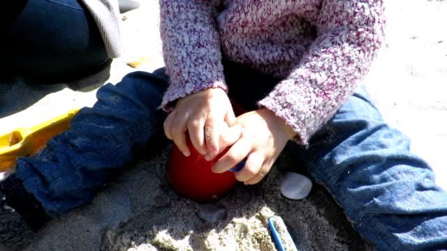 barnet leker med stenar i skopan sitter på sand beach - byxor bildbanksvideor och videomaterial från bakom kulisserna