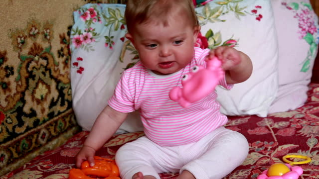 Baby playing with toys on the bed video