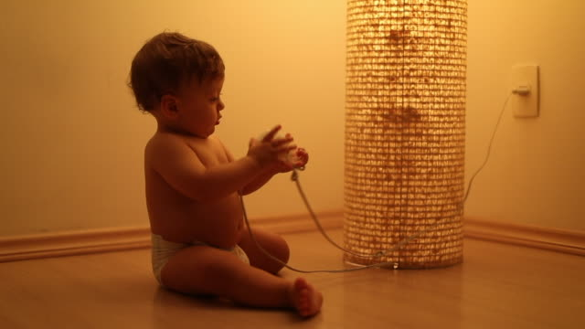 Baby plays with lamp object