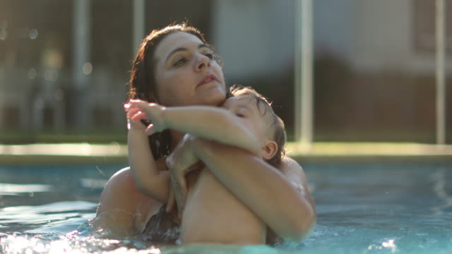 Baby pulling mother hair at the pool. Real life authentic child pulls mom hair