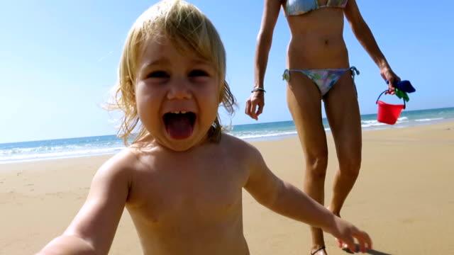 baby pursues camera at beach