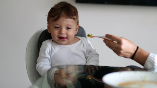 vídeos de stock e filmes b-roll de baby rejecting food, mother trying to feed one year old infant toddler - desperdício alimentar