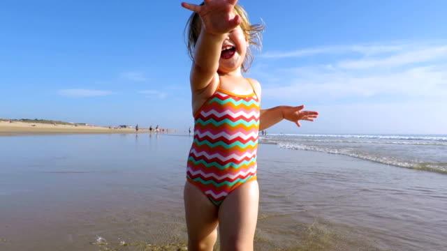 baby running in ocean video
