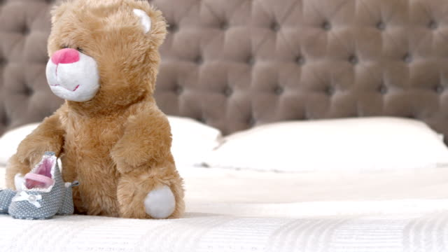 Baby shoes and teddy bear on bed video