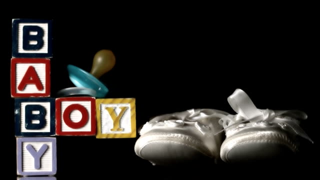 Baby shoes falling besides baby blocks and blue smoother Baby shoes falling besides baby blocks and blue smoother on black background in slow motion baby booties stock videos & royalty-free footage