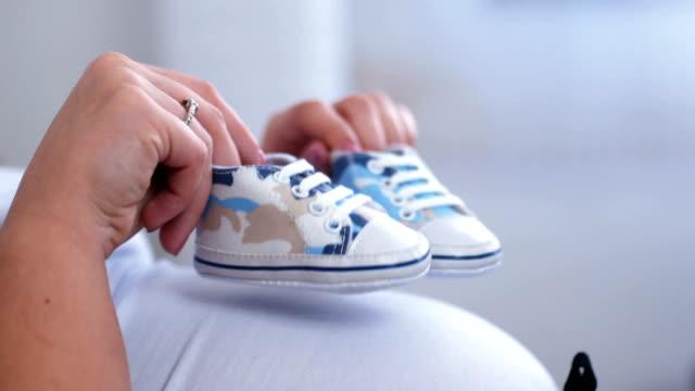 baby-schuhe auf den schwangeren bauch - schwanger stock-videos und b-roll-filmmaterial