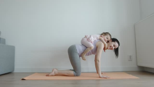 YOGA: Baby sits on her mother's back who does yoga mat at home - Side view YOGA: Baby sits on her mother's back who does yoga mat at home - Side view yoga stock videos & royalty-free footage